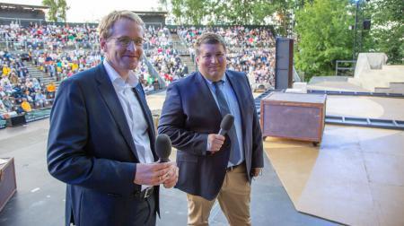Der Geschäftsführer der Eutiner Festspiele, Falk Herzog, und Ministerpäsident Daniel Günther stehen auf einer Bühne.