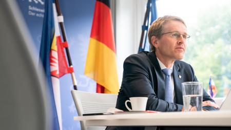 Ministerpräsident Günther sitzt an einem Schreibtisch und schaut auf einen großen Bildschirm. Hinter ihm sind die Flaggen von Deutschland, Europa und Schleswig-Holstein aufgestellt.