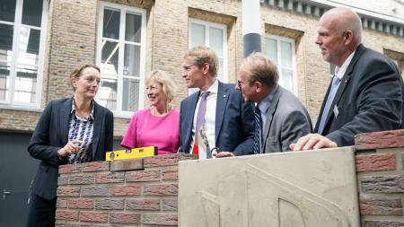 Ministerpräsident Daniel Günther bei der Eröffnung der NordBau. Er steht hinter einer halbhohen Backsteinmauer.