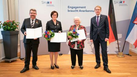 Die Ausgezeichneten stehen mit Ministerpräsident Günther in einem Raum und halten ihre Urkunden in den Händen.