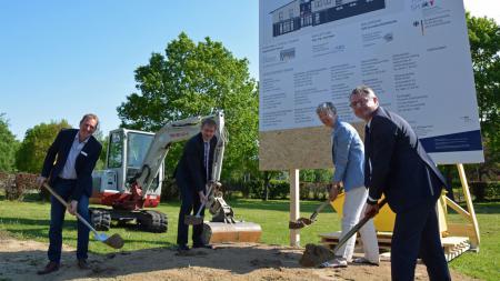 Eine Frau und drei Männer haben je einen Spaten in der Hand und stehen vor einem Schild auf dem steht: Neubau MarktTreff Brekendorf.