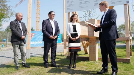 Ministerpräsident Daniel Günther steht gemeinsam mit drei anderen Personen vor einem Bauschild und liest einen Förderbescheid vor.