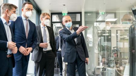 Gesundheitsminister Garg, Bundesminister Spahn und Ministerpräsident Günther stehen vor einer Glasscheibe und lassen sich ein technisches Gerät erklären.