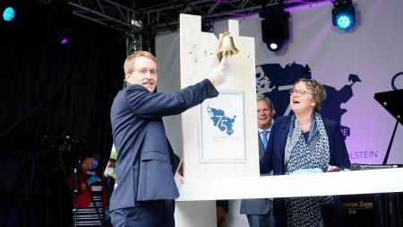 Ministerpräsident Daniel Günther steht auf einer Bühne und läutet eine Glocke.
