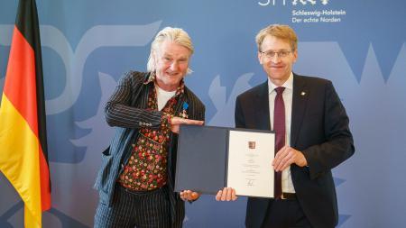 Ministerpräsident Daniel Günther steht neben dem Ausgezeichneten, Detlev Buck. Sie halten gemeinsam eine Urkunde in die Höhe.