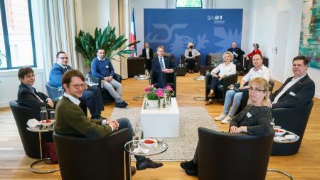 Ministerpräsident Daniel Günther sitzt mit acht Personen um einen Tisch herum.