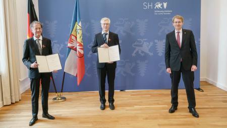 Lutz Hennings (v.l.), Diethard Tautz und Ministerpräsident Daniel Günther bei der Ehrung in Kiel.