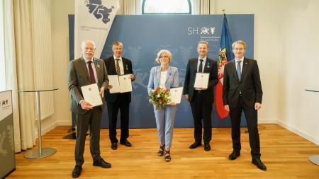 Ministerpräsident Daniel Günther mit den vier Ausgezeichneten.