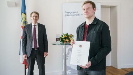 Ministerpräsident Daniel Günther und der ausgezeichnete Till Barne Tegge stehen mit Abstand in einem Raum. Tegge hält eine Urkunde in der Hand.