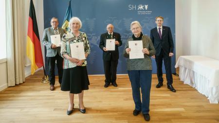 Die Ausgezeichneten Thies Thomsen, Ursula Hör, Johannes Erichsen und Ingrid Doll sowie Ministerpräsident Günther stehen mit einem coronabedingten Abstand in einem Raum. Sie halten Urkunden in den Händen.