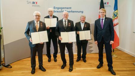 Die Ausgezeichneten Peter Sönnichsen (von links), Dieter Wade, Walter Behrens, Wolfgang Engelmann mit Ministerpräsident Daniel Günther