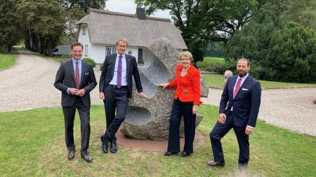 Ministerpräsident Daniel Günther steht mit drei weiteren Personen vor einem kunstvoll bearbeiteten Findling im Steinpark Warder.