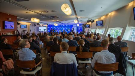 In einem Raum sitzen viele Menschen und hören drei Experten auf einem Podium zu.