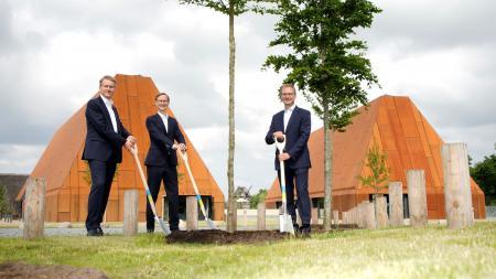 Ministerpräsident Günther, Marc Fielmann und Guido Wendt stehen neben einem frisch gepflanzten Baum halten Spaten in den Händen.
