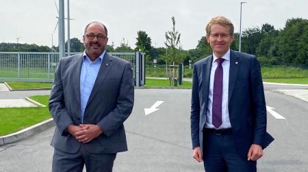 Ministerpräsident Daniel Günther und der Direktor der ALDI Regionalgesellschaft, Stefan Buttkus, stehen auf einem Parkplatz.