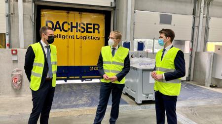 Drei Männer stehen in einer Lagerhalle. Sie alle tragen Masken und gelbe Warnwesten über ihren Anzügen. Im Hintergrund steht auf einem Container: Dachser Intelligent Logistics.