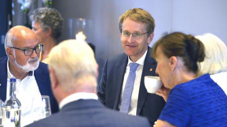 Ministerpräsident Daniel Günther sitzt mit vier weiteren Menschen an einem Tisch.