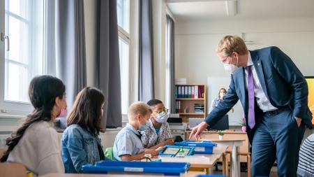 Ministerpräsident Daniel Günther spricht mit vier Schüler:innen der Gerhart-Hauptmann-Schule in Kiel.