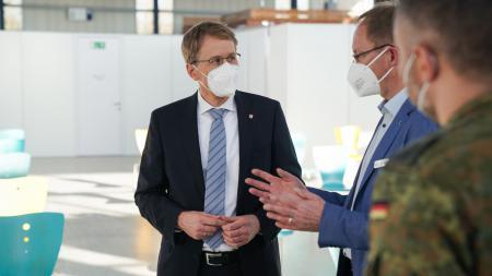 Ministerpräsident Daniel Günther steht in einem großen Raum und unterhält sich mit zwei Personen. Eine der Personen trägt eine Bundeswehr-Uniform.