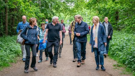 Eine Menschengruppe wandert gemeinsam durch ein Waldstück.