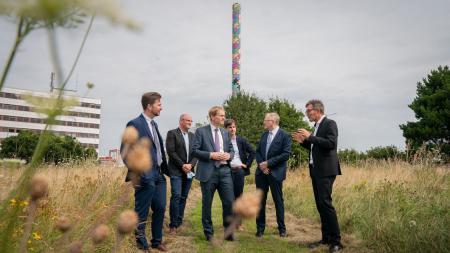 Ministerpräsident Daniel Günther mit der Covestro-Geschäftsleitung vor einer Blühwiese.
