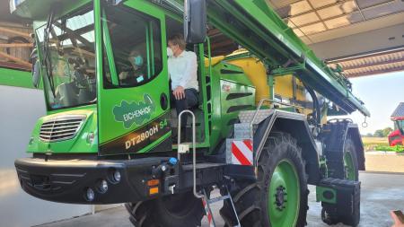 Ministerpräsident Daniel Günther sitzt auf einer großen Landmaschine.