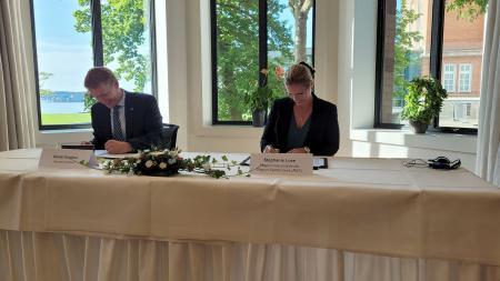 Ministerpräsident Daniel Günther und die Regionsratsvorsitzende Stephanie Lose unterzeichnen eine gemeinsame Erklärung.